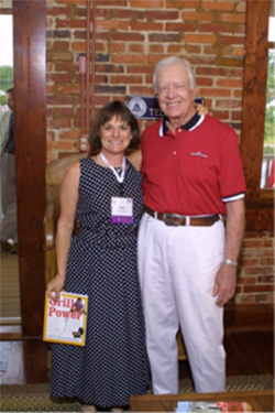 Holly presents Grill Power to President Jimmy Carter when she was a judge at his Plains Peanut Festival cooking contest